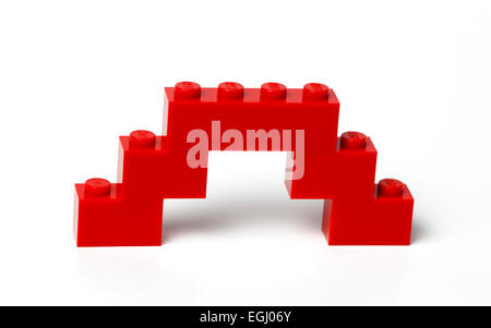 A  bridge or viaduct construction in red interlocking Lego bricks on white. - Stock Photo