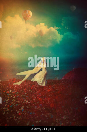 young woman in white dress dancing on the cliff - Stock Photo