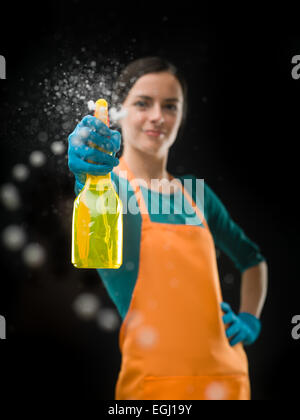 portrait of cleaning woman aiming spray bottle in front of her, on black background - Stock Photo