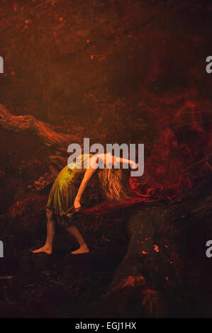 young woman dancing in nature holding red shawl - Stock Photo