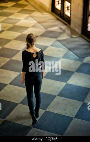 Young woman walking on tiled floor, - Stock Photo