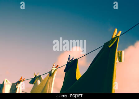 Close-up view of clothes on a clothesline held with clothes pegs at sunset - Stock Photo