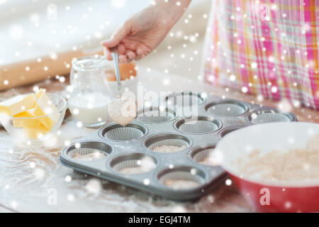 close up of woman filling muffins molds with dough - Stock Photo