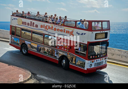 Tourists in an open-top double-decker bus on an excursion at the coast, Malta - Stock Photo