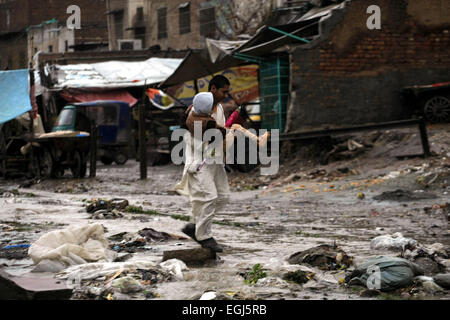 Peshawar, Pakistan. 25th Feb, 2015. A man carries a child as he crosses a waterlogged street after heavy rain in - Stock Photo