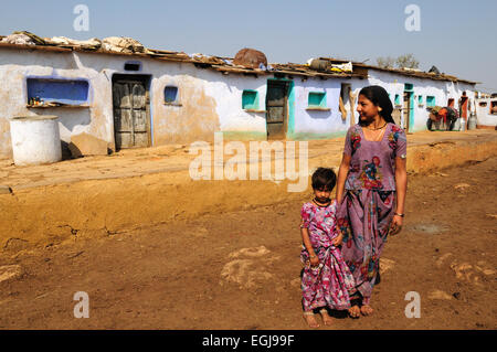 Indian woman and daughter standing outside tribal village houses Kalpi Village Rajasthan India - Stock Photo