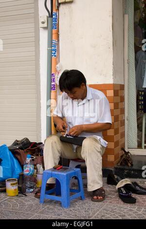 Street shoemaker repairing shoes, Saigon, Ho Chi Minh City, Vietnam, Asia - Stock Photo