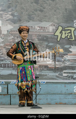 Dong man in ethnic attire playing a pipa, Zhaoxing Dong village, Guizhou Province, China - Stock Photo