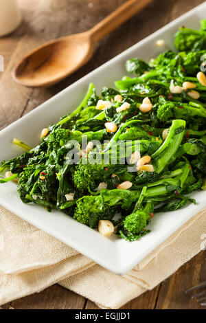 Homemade Sauteed Green Broccoli Rabe with Garlic and Nuts - Stock Photo