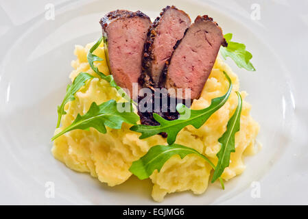 Spice crusted veal liver sliced to with balsamic vinegar caramelized onions, mashed potatoes and rocket on a vintage - Stock Photo