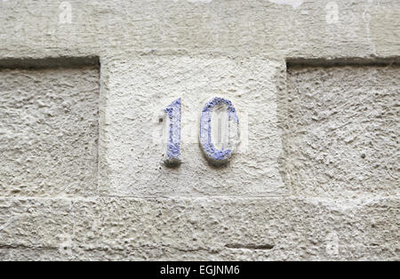 Number ten on a stone wall, detail of a number of information on a wall in the city, ancient and old - Stock Photo