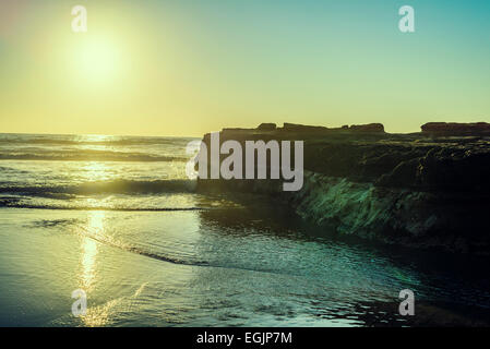 The Sun setting with a view of Flat Rock on Torrey Pines State Beach. La Jolla, California, United States. - Stock Photo