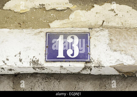 Number thirteen on a wall, detail of a number of information in a house - Stock Photo