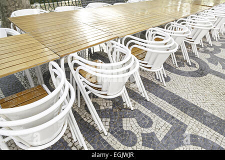 Terrace tables and chairs, detail of a land in a city street - Stock Photo