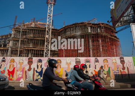 Motorcyclists pass in front of a mall building construction work area in Jakarta coastal area. - Stock Photo