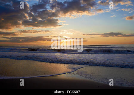 Sunset or sunrise over sea with clouds - Stock Photo
