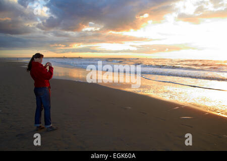 woman taking a picture with the sun behind on cold sandy seashore - Stock Photo
