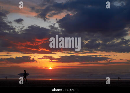 Surfer on the ocean beach at sunset with dark clouds - Stock Photo