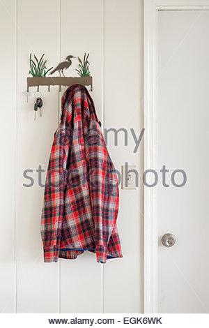 Plaid shirt hanging on coat hook on white wall - Stock Photo