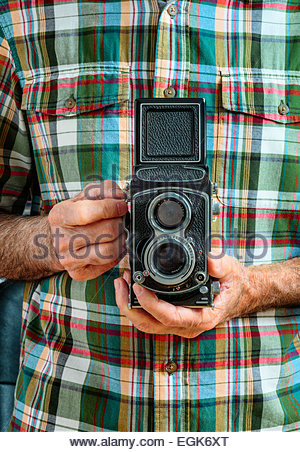 Man wearing plaid shirt holding vintage photo camera - Stock Photo