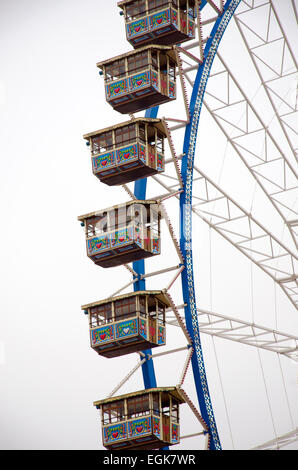 Ferris wheel detail and cabins in a cloudy sky and white - Stock Photo