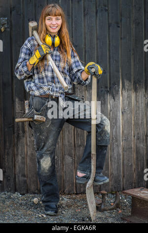 Girl in construction worker clothings standing with a shovel and hammer in front of a barn - Stock Photo