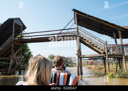 Going under wooden bridge.Tourists on Speed boat ,longboat,long tailed engined boat on waterway canal of Inle Lake,Burma,Myanmar - Stock Photo