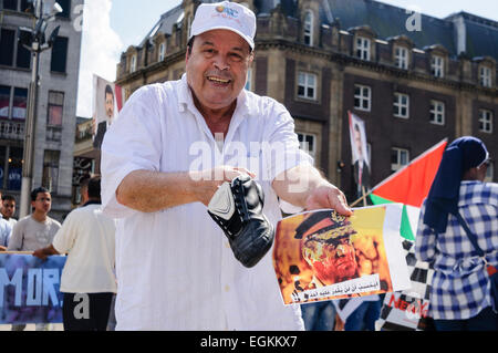 Amsterdam, The Netherlands, 4th August 2013 - An Egyptian man hits a photograph of General Sisi with a shoe as Egyptians - Stock Photo