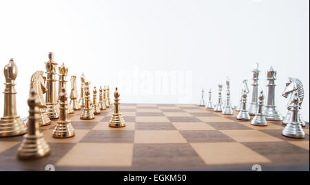Chess set with gold and silver pieces on a wooden board.  The gold pawn piece has made the first move. - Stock Photo