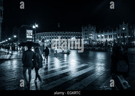 People under umbrellas on a rainy night on the streets of Valencia in Spain on a pedestrian crossing - Stock Photo