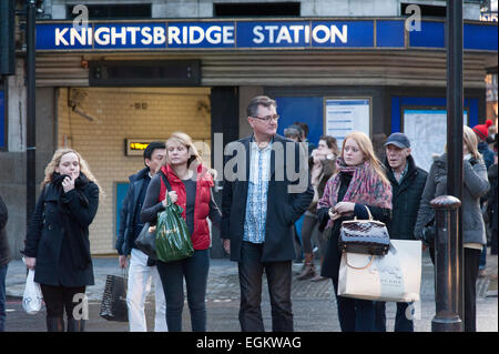 Shoppers crossing the road outside Knightsbridge Underground station in London. - Stock Photo