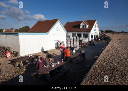 Customers sitting outside the Bluebird beach cafe on Ferring beach in the winter sunshine - Stock Photo