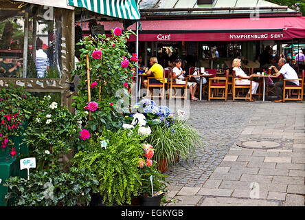 An open air coffee near a flowers stall offers leisure to the shoppers of the Viktualienmarkt,  famous market in - Stock Photo