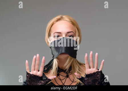 girl with self-adhesive tape over her mouth on gray - Stock Photo