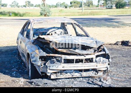 A stolen car burnt beside a main road - Stock Photo