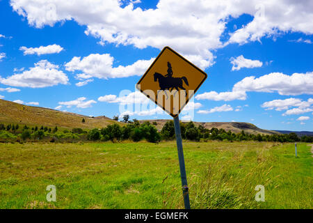 Horse riding sign in the Australian bush on a sunny day with blue sky. - Stock Photo