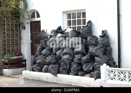 London, UK, 14 December 2014, Pile of black rubbish bags outside suburan terraced house in Greenwich Village. - Stock Photo