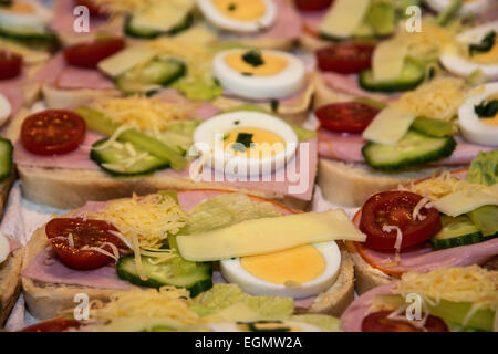 Sandwiches with egg, cheese, cucumber, ham and cherry tomatoes. Food and drink theme. - Stock Photo