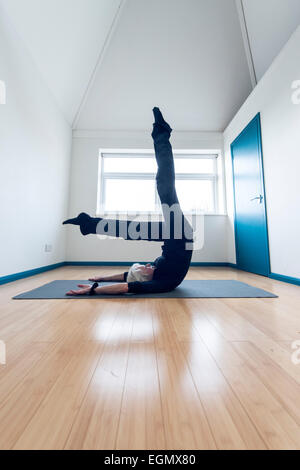 elderly older lady practicing palates yoga and keeping active while being very flexible in some unusual positions, - Stock Photo