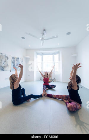 three women partake in a group yoga fitness class, in an empty room. The idea is that you rely on your partners - Stock Photo