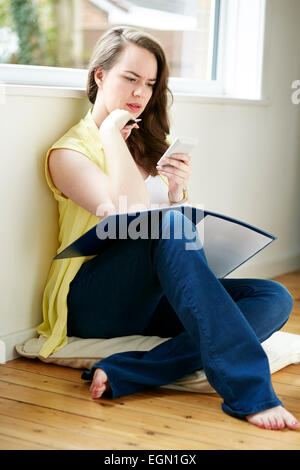 Woman working out finances sat on floor - Stock Photo