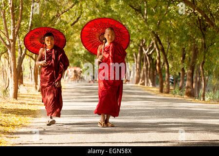 Two burmese buddhist monks walking along a road, Bagan, Myanmar ( Burma ), Asia - Stock Photo
