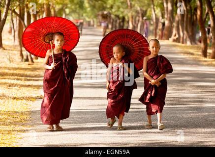 Three young buddhist monks walking along a road, Bagan, Myanmar ( Burma ), Asia - Stock Photo