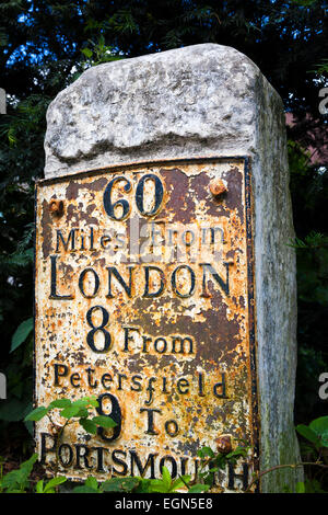 Old worn traditional milestone marker with metal plate stating 60 miles from London and 9 to Portsmouth - Stock Photo