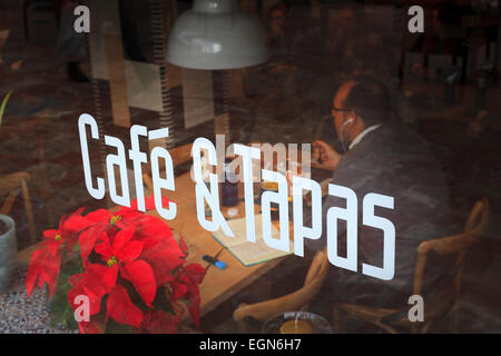 Cafe and Tapas sign on window with diner eating inside - Stock Photo