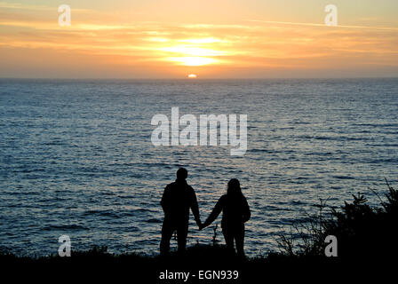 man and woman hold hands while watching sunset in Mendocino California USA - Stock Photo
