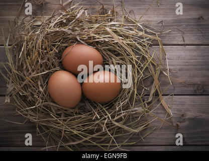 Eggs in hay nest on old wooden table background, top view - Stock Photo