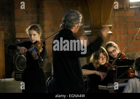 Riga Latvia. Conductor, lead violinist and members of youth orchestra during classical music recital inside Saint - Stock Photo