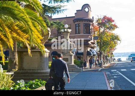 A young man walking past the entrance to a park on Bridgeway in Sausalito, California. - Stock Photo