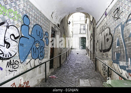 Old alley in Lisbon, detail of an old and battered city street, old town - Stock Photo